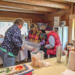 Karen, Chris, and Donna organize the kitchen